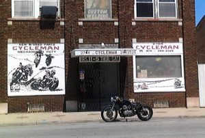 A bobber style motorcycle sits curbside in front of Cycle Man Motorcycle Shop on Lagrange Street in Toledo Ohio