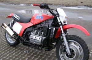 A custom built enduro inspired Goldwing GL1500 fitted with red plastics and knobby tires like the Honda XR bikes.