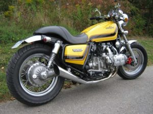 An early Honda Goldwing motorcycle featuring a Yellow with black and red paint scheme.
