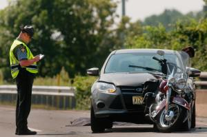 Police Officer filling out a crash report. Standing next to a motorcycle that has been rear-ended by a distracted driver.