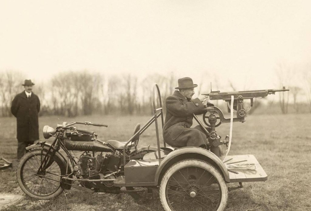 An early Indian Motorcycle Trike, fitted with a rearward facing automatic rifle and seat for a tailgunner.