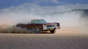 Bronze colored Cadillac Eldorado convertible in a dust cloud.