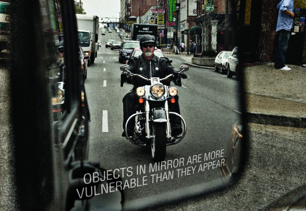 Motorcyclist approaching in vehicle mirror. Text on bottom of mirror reads, Objects in mirror are more vulnerable than they appear.