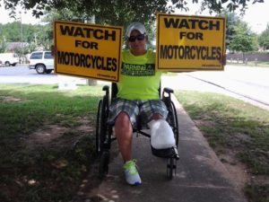 A man with a bandaged leg stump sits in a wheelchair holding two yellow signs that read Watch for Motorcycles.