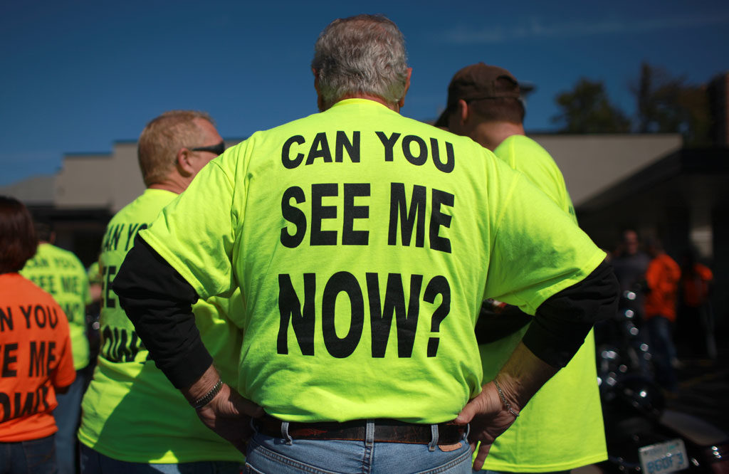 "Man wearing safety green tee shirt from behind. Text on shirt reads "" Can You See Me Now?"""