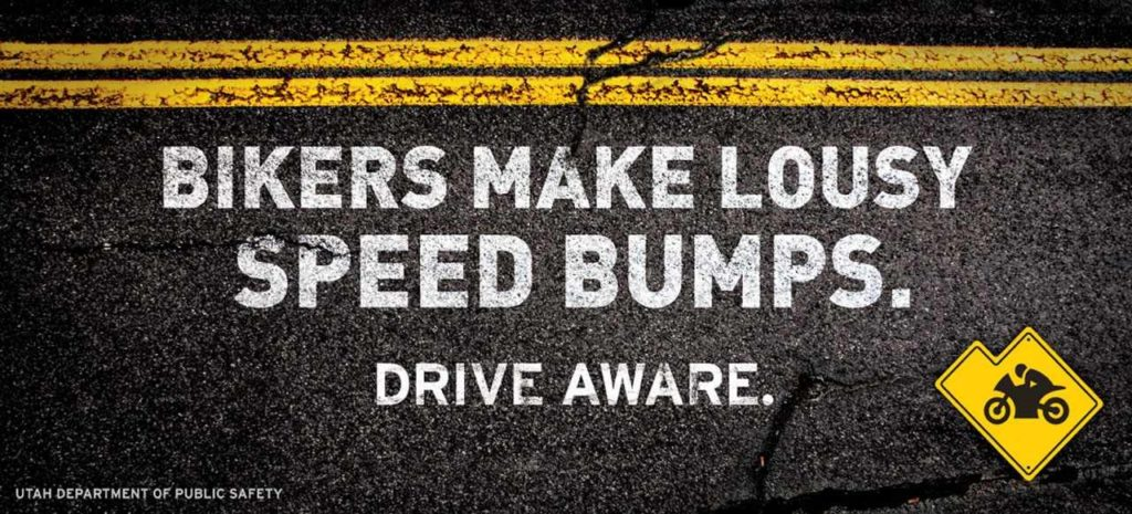 An infographic with double yellow line on asphalt. Text reads Bikes Make Lousy Speed Bumps. Drive Aware.
