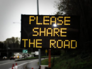 Photo of illuminated road construction sign that reads, Please Share The Road.