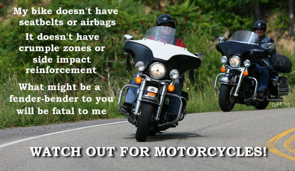 Two motorcycles approaching in a turn on asphalt roadway. The text reminds motorists to watch out for motorcycles because they do not have airbags and crumple zones.