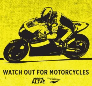 Bright Yellow backgwound with single color Black image of sportbike and rider entering a turn. Text reads - Watch Out For Motorcycles. Arrive Alive.