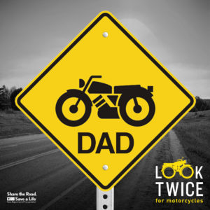 Yellow road sign with silhouette of motorcycle and the word DAD.