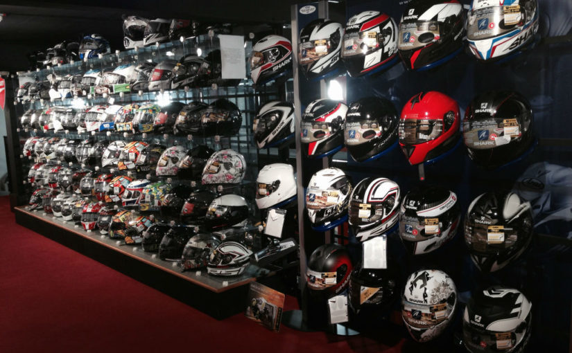 Approximately 80 Motorcycle Helmets on a display wall of a motorcycle dealership