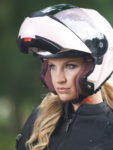 A blonde haired female motorcyclist wearing a white modular style helmet with the chinbar up.