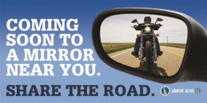 Motorcycle Awareness Month PSA with a Motorcycle approaching, pictured in the driver's side mirror.