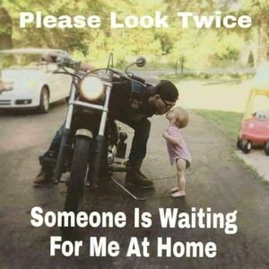 biker sitting on motorcycle leans over to kiss a toddler standing next to the bike. The text of the meme reads Please look Twice. Someone is Waiting for Me at Home.