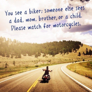A biker rides away on a road that curves off into the hilly tree covered distance with text in the top of the image.